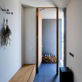 神戸の小さい片開きドアモダンスタイルのおしゃれな玄関ホール (白い壁、木目調のドア、黒い床) の写真