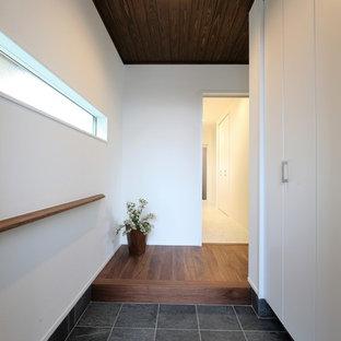 Ispirazione per un ingresso o corridoio etnico con pareti bianche e pavimento nero