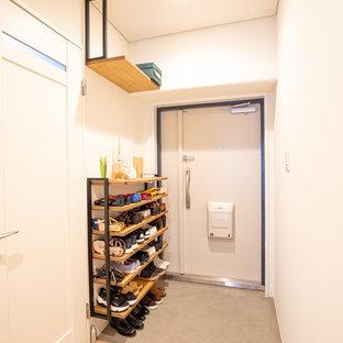 大阪の小さい片開きドアアジアンスタイルのおしゃれな玄関ホール (白い壁、コンクリートの床、白いドア、グレーの床) の写真