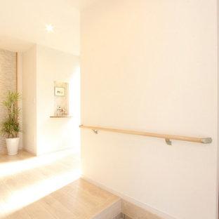 福岡の中くらいの片開きドアコンテンポラリースタイルのおしゃれな玄関ホール (白い壁、合板フローリング、茶色いドア、ベージュの床、クロスの天井、壁紙) の写真