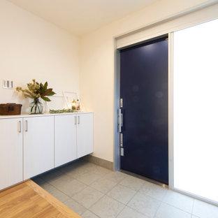 Inredning av en modern hall, med vita väggar, en enkeldörr och en blå dörr