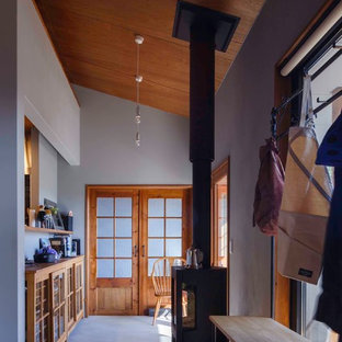 Esempio di un corridoio stile rurale di medie dimensioni con pareti grigie, pavimento in cemento, una porta scorrevole, una porta in legno bruno e pavimento grigio