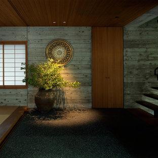 Foto de hall de estilo zen, grande, con paredes grises, suelo de cemento, puerta doble, puerta de madera en tonos medios y suelo negro