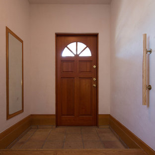 Example of a terra-cotta floor and beige floor entryway design in Other with white walls and a brown front door