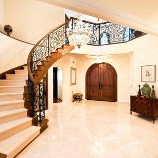他の地域の両開きドアトラディショナルスタイルのおしゃれな玄関ホール (ベージュの壁、大理石の床、濃色木目調のドア、ベージュの床) の写真