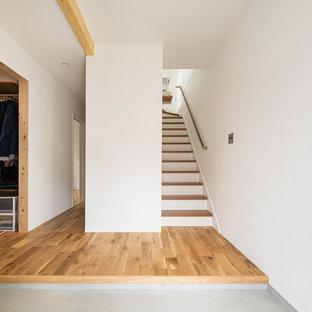 他の地域のアジアンスタイルのおしゃれな玄関 (白い壁、コンクリートの床、グレーの床) の写真