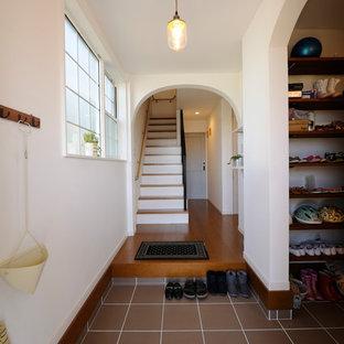 他の地域のミッドセンチュリースタイルのおしゃれな玄関 (白い壁、茶色い床) の写真
