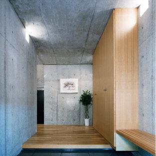 東京23区の広い片開きドアインダストリアルスタイルのおしゃれな玄関ホール (グレーの壁、セラミックタイルの床、木目調のドア、グレーの床) の写真