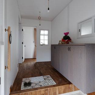 他の地域のインダストリアルスタイルのおしゃれな玄関ホール (白い壁、ベージュの床) の写真