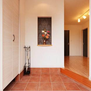 Foto de hall de estilo de casa de campo, grande, con paredes blancas, suelo de baldosas de terracota, puerta simple, puerta de madera en tonos medios y suelo marrón