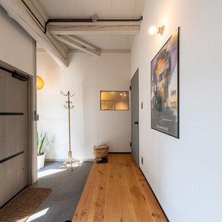 他の地域の片開きドアインダストリアルスタイルのおしゃれな玄関ロビー (白い壁、無垢フローリング、グレーのドア、茶色い床) の写真