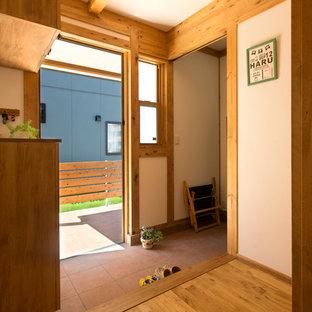 名古屋のアジアンスタイルのおしゃれな玄関ホール (白い壁、テラコッタタイルの床、茶色い床) の写真
