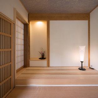 東京都下の大きい引き戸和風のおしゃれな玄関ホール (白い壁、淡色無垢フローリング、淡色木目調のドア、ベージュの床) の写真