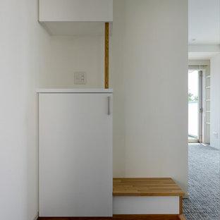 Imagen de entrada industrial, grande, con paredes blancas, suelo vinílico, puerta simple, puerta marrón y suelo negro