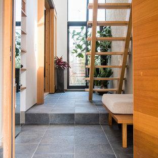 Idée de décoration pour une entrée minimaliste de taille moyenne avec un couloir, un mur blanc, un sol en carrelage de porcelaine, une porte simple, une porte en bois brun et un sol gris.