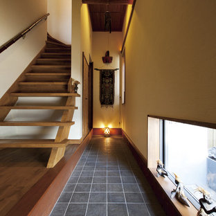 他の地域のアジアンスタイルのおしゃれな玄関 (ベージュの壁、黒い床) の写真