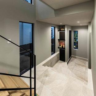 Modern inredning av en mellanstor entré, med grå väggar, klinkergolv i keramik, en dubbeldörr, en svart dörr och grått golv