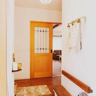 他の地域の地中海スタイルのおしゃれな玄関 (白い壁、テラコッタタイルの床、茶色い床) の写真