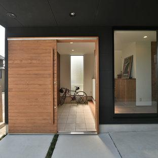 Cette photo montre une entrée asiatique avec un mur noir, une porte coulissante, une porte en bois clair et un sol gris.