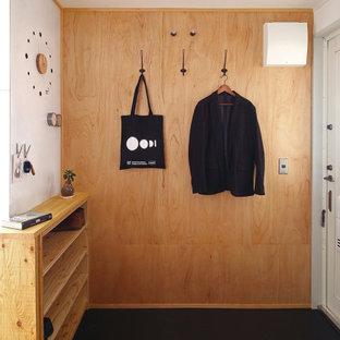 Minimalistisk inredning av en hall, med vita väggar, mörkt trägolv, en enkeldörr, en vit dörr och beiget golv