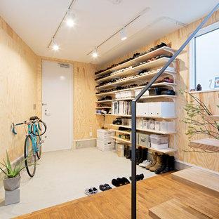 東京23区の片開きドアインダストリアルスタイルのおしゃれな玄関ロビー (コンクリートの床、白いドア、茶色い床) の写真