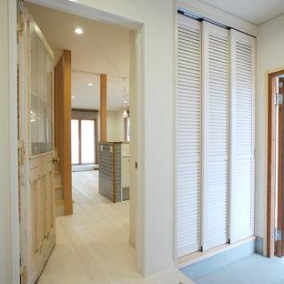 他の地域の片開きドア北欧スタイルのおしゃれな玄関ホール (白い壁、淡色無垢フローリング、木目調のドア、白い床) の写真