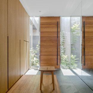 東京23区の片開きドアモダンスタイルのおしゃれな玄関 (茶色い壁、木目調のドア、茶色い床) の写真