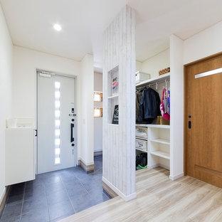 Nordisk inredning av en hall, med vita väggar, en enkeldörr, en vit dörr, målat trägolv och vitt golv
