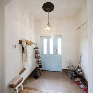 東京23区の片開きドア地中海スタイルのおしゃれな玄関ホール (白い壁、青いドア、茶色い床) の写真