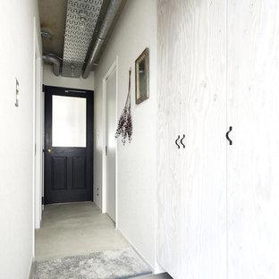 他の地域のインダストリアルスタイルのおしゃれな玄関ホール (白い壁、コンクリートの床、グレーの床) の写真