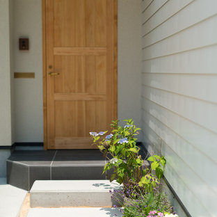 Example of an urban ceramic floor and black floor entryway design in Other with beige walls and a light wood front door
