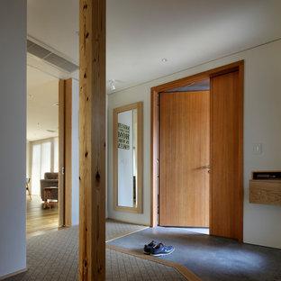 東京23区の広い片開きドアアジアンスタイルのおしゃれな玄関ホール (白い壁、カーペット敷き、木目調のドア、茶色い床) の写真