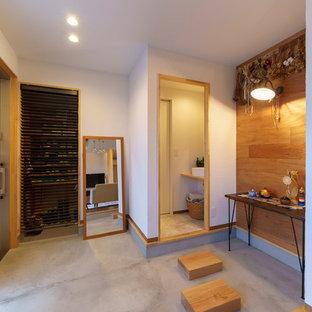 他の地域の小さい引き戸アジアンスタイルのおしゃれな玄関 (茶色い床、白い壁、コンクリートの床、金属製ドア) の写真