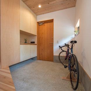 横浜の片開きドアアジアンスタイルのおしゃれな玄関ホール (白い壁、木目調のドア、グレーの床) の写真