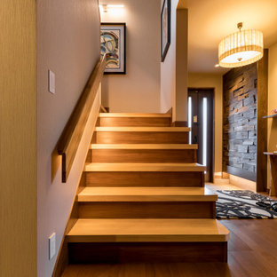 他の地域の小さい両開きドアコンテンポラリースタイルのおしゃれな玄関ホール (ベージュの壁、合板フローリング、茶色いドア、茶色い床) の写真