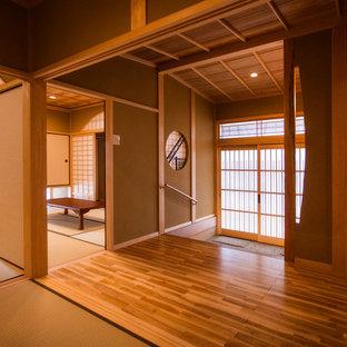 他の地域の引き戸アジアンスタイルのおしゃれな玄関 (茶色い壁、御影石の床、グレーの床) の写真