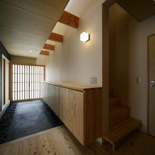 Foto di un ingresso o corridoio etnico con pareti bianche, una porta scorrevole e una porta in legno chiaro