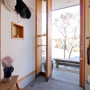 東京都下の引き戸和風のおしゃれな玄関 (白い壁、木目調のドア、グレーの床) の写真