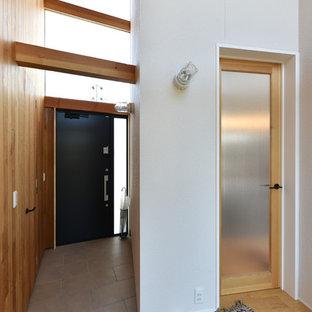 他の地域, の片開きドアアジアンスタイルのおしゃれな玄関 (白い壁、黒いドア、グレーの床) の写真