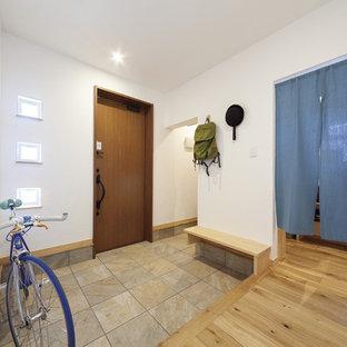 他の地域の中サイズの片開きドアモダンスタイルのおしゃれな玄関ホール (白い壁、濃色木目調のドア、ベージュの床) の写真