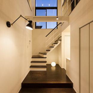 Cette photo montre une petit entrée rétro avec un couloir, un mur blanc, un sol en contreplaqué et un sol noir.