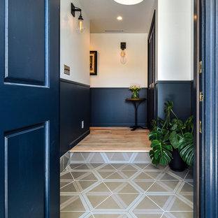 東京23区の片開きドアトランジショナルスタイルのおしゃれな玄関 (青い壁、青いドア、マルチカラーの床) の写真