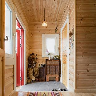他の地域の片開きドア北欧スタイルのおしゃれな玄関 (茶色い壁、赤いドア、グレーの床) の写真