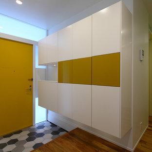 東京23区の中くらいの片開きドアモダンスタイルのおしゃれな玄関ホール (白い壁、無垢フローリング、黄色いドア、茶色い床) の写真