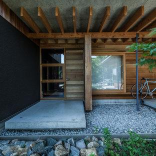 他の地域の中サイズの片開きドアコンテンポラリースタイルのおしゃれな玄関 (茶色い壁、コンクリートの床、茶色いドア、グレーの床) の写真