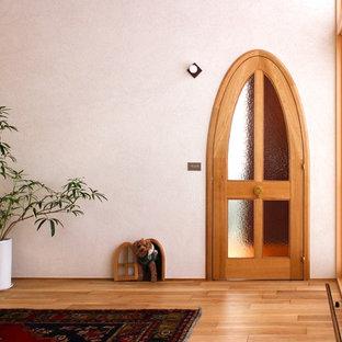 札幌の片開きドアアジアンスタイルのおしゃれな玄関 (白い壁、淡色無垢フローリング、淡色木目調のドア、ベージュの床) の写真