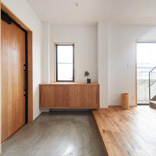 他の地域の片開きドアインダストリアルスタイルのおしゃれな玄関ホール (白い壁、コンクリートの床、木目調のドア、グレーの床) の写真