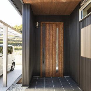 Foto de entrada urbana con paredes negras, suelo de baldosas de porcelana, puerta simple, puerta de madera en tonos medios y suelo negro