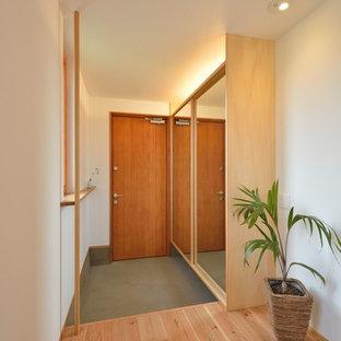 他の地域の片開きドアアジアンスタイルのおしゃれな玄関ホール (白い壁、木目調のドア) の写真