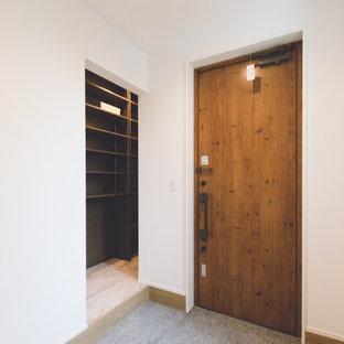 Foto di un ingresso o corridoio scandinavo di medie dimensioni con pareti bianche, pavimento in granito, una porta singola e una porta in legno bruno